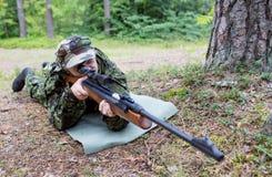 Giovane soldato o cacciatore con la pistola in foresta Fotografia Stock Libera da Diritti