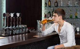 Giovane solo che beve da solo al pub Fotografia Stock