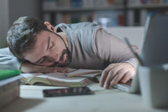 Giovane sonnolento allo scrittorio Immagine Stock