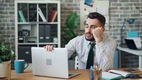 Giovane sonnolento che lavora con il computer portatile in ufficio poi che fa un sonnellino sullo scrittorio archivi video