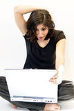 Giovane sorpresa dei ritrovamenti della donna del Brunette sul calcolatore Fotografia Stock Libera da Diritti