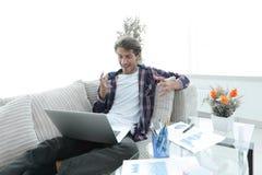 Giovane sorpreso con il computer portatile che si siede sul sofà Immagini Stock Libere da Diritti