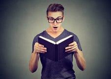 Giovane sorpreso in vetri che legge un libro Fotografia Stock Libera da Diritti