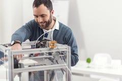 Giovane sorridente che installa stampante 3D Fotografia Stock Libera da Diritti