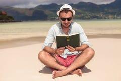 Giovane sorridente che legge un libro sulla spiaggia Fotografia Stock Libera da Diritti