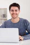 Giovane sorridente che per mezzo di un computer portatile Immagine Stock