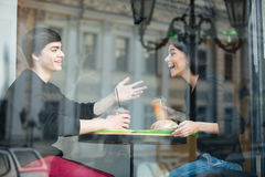 Giovane sorridente che si siede in caffè con il suo succo bevente della sorella Immagini Stock