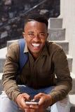 Giovane sorridente che si siede con il telefono cellulare Fotografie Stock Libere da Diritti