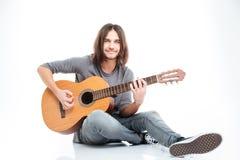 Giovane sorridente che si siede sul pavimento e sul gioco della chitarra Fotografia Stock