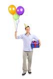 Giovane sorridente che tiene un presente e i baloons Immagini Stock