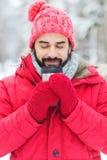 Giovane sorridente con la tazza nella foresta di inverno fotografia stock
