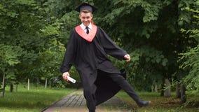 Giovane sorridente in diploma di trasporto del vestito accademico in mani, saltanti con la gioia archivi video