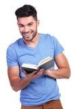 Giovane sorridente felice che legge un libro immagini stock libere da diritti