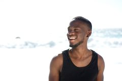 Giovane sorridente felice che sta alla spiaggia Immagine Stock Libera da Diritti