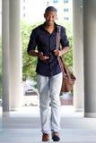 Giovane sorridente integrale che cammina nella città con il telefono cellulare e la borsa Fotografia Stock Libera da Diritti