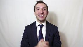 Giovane sorridere bello dell'uomo d'affari e mani attivamente d'applauso, accoglienti i nuovi clienti stock footage