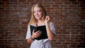 Giovane sorridere biondo caucasico, libro di lettura ed esaminare la macchina fotografica, ritratto, muro di mattoni nei preceden archivi video