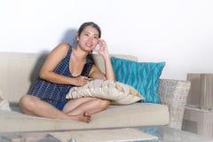 Giovane sorridere cinese asiatico sveglio della donna felice sedendosi a casa lo strato del sofà che guarda manifestazione di TV  immagine stock