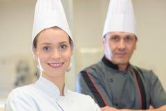 Giovane sorridere cucina i clienti di saluto alla cucina dei bistrot immagine stock