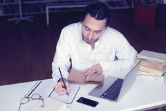Giovane sorridere dello studente universitario o dell'uomo d'affari, lavorante al computer portatile che legge un libro in una bi Immagine Stock Libera da Diritti
