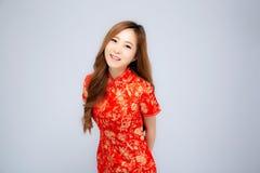Giovane sorriso asiatico del cheongsam di usura di donna del bello nuovo anno cinese felice del ritratto con la congratulazione e fotografia stock libera da diritti