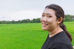Giovane sorriso teenager asiatico innocente sveglio con il giacimento verde del riso Fotografia Stock