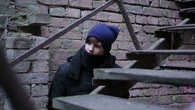 Giovane sospettoso che spia su qualcuno, nascondendosi dagli spacconi, fuga dalla casa stock footage