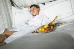Giovane splendido (signore) che si trova su un letto all'hotel Fotografie Stock