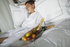 Giovane splendido (signore) che si trova su un letto all'hotel Fotografie Stock Libere da Diritti