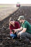 Giovane sporcizia dell'esame degli agricoltori mentre il trattore sta arando il campo immagini stock libere da diritti