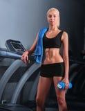 Giovane sportiva attraente che riposa dopo avere corso sulla pedana mobile Immagine Stock Libera da Diritti