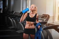 Giovane sportiva attraente che riposa dopo avere corso sulla pedana mobile Fotografia Stock