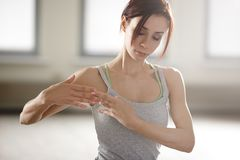 Giovane sportiva rilassata che fa yoga e che medita nello studio Fotografie Stock
