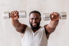 Giovane sportivo africano arrabbiato che si esercita con i pesi della mano Fotografie Stock Libere da Diritti