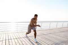 Giovane sportivo afroamericano senza camicia che fa gli edifici occupati sul pilastro Fotografie Stock