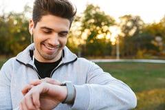 Giovane sportivo bello all'aperto nella musica d'ascolto del parco con le cuffie che esaminano orologio fotografie stock