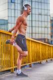 Giovane sportivo che fa allungando esercizio sul ponte Fotografia Stock