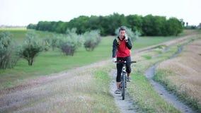 Giovane sportivo che parla sul telefono che guida una bici video d archivio