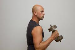 Giovane sportivo lavorante duro che fa allenamento con la testa di legno Fotografia Stock Libera da Diritti
