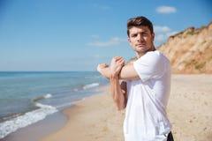 Giovane sportivo sicuro che fa gli esercizi sulla spiaggia Immagine Stock Libera da Diritti