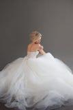 Giovane sposa affascinante in vestito da sposa lussuoso Ragazza graziosa nel bianco Fondo grigio back fotografia stock