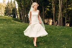 Giovane sposa bionda che cammina lungo l'erba in un parco esotico Fotografia Stock Libera da Diritti