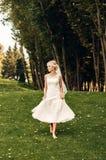 Giovane sposa bionda che cammina lungo l'erba in un parco esotico Fotografie Stock