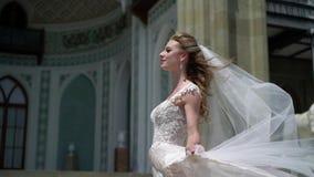 Giovane sposa che posa in una città Velo d'ondeggiamento al giorno di estate ventoso stock footage