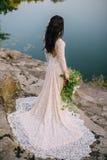 Giovane sposa che sta sulla sponda del fiume rocciosa, tramonto Fotografie Stock