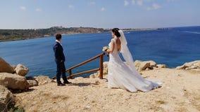 Giovane sposa e sposo che camminano sulla spiaggia, sul baciare e sul divertiresi archivi video