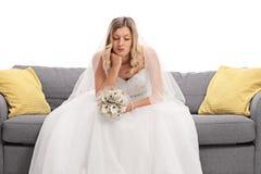 Giovane sposa preoccupata che si siede su un sofà immagine stock libera da diritti