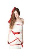 Giovane sposa spostata con i nastri rossi Immagini Stock Libere da Diritti