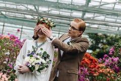 giovane sposo alla moda in occhiali che chiudono gli occhi alla bella sposa della testarossa fotografie stock libere da diritti