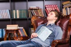 Giovane stanco che si appisola nella biblioteca Immagine Stock